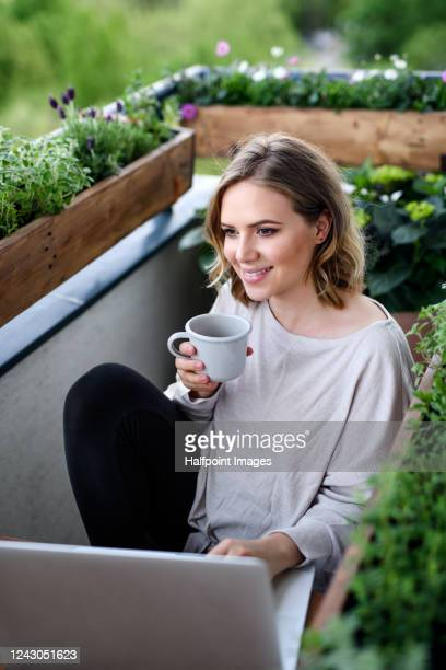 portrait of  happy young woman on balcony with flowering plants, relaxing with coffee. - active lifestyle stock pictures, royalty-free photos & images