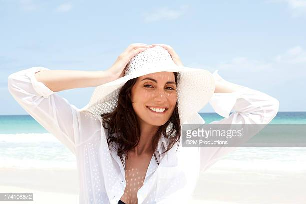 portrait of happy young woman on beach - sun hat stock pictures, royalty-free photos & images