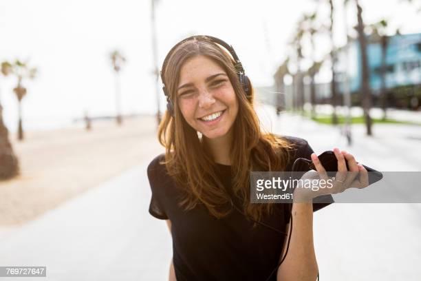 portrait of happy young woman on boardwalk listening to music - t shirt preta imagens e fotografias de stock