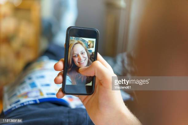 portrait of happy young woman on display of cell phone skyping with her boyfriend lying on the couch - voip stockfoto's en -beelden