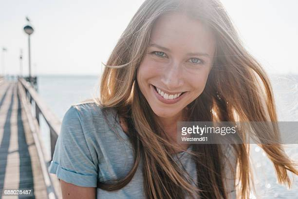 portrait of happy young woman on jetty at backlight - attraktive frau stock-fotos und bilder