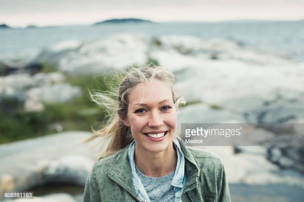 portrait of happy young woman on rock by sea - nordic countries stock pictures, royalty-free photos & images
