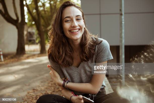 portrait of happy young woman outdoors - lachen stock-fotos und bilder