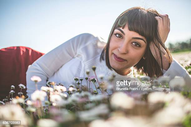 portrait of happy young woman relaxing on flowers field - cheveux courts photos et images de collection