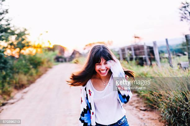 Portrait Of Happy Young Woman Running On Road Amidst Plants Against Clear Sky