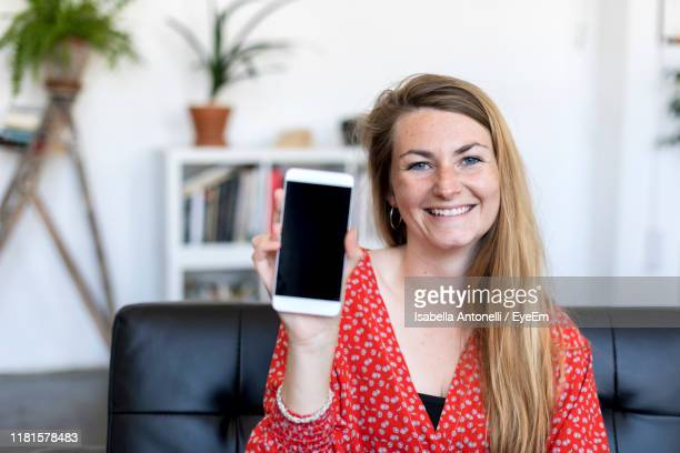 portrait of happy young woman showing blank phone while sitting on sofa at home - mostrare foto e immagini stock