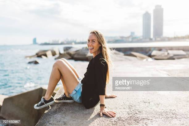portrait of happy young woman sitting at the seafront - denim shorts stock pictures, royalty-free photos & images