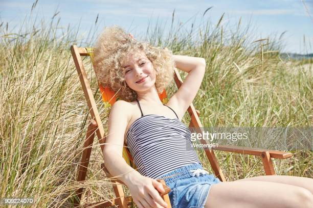 Portrait of happy young woman sitting on beach chair in the dunes