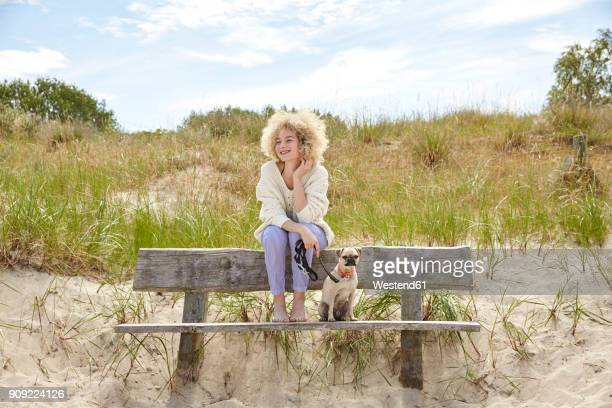 Portrait of happy young woman sitting on bench in the dunes with her dog