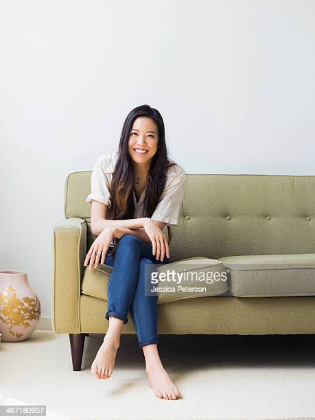 portrait of happy young woman sitting on sofa - sitting stock pictures, royalty-free photos & images