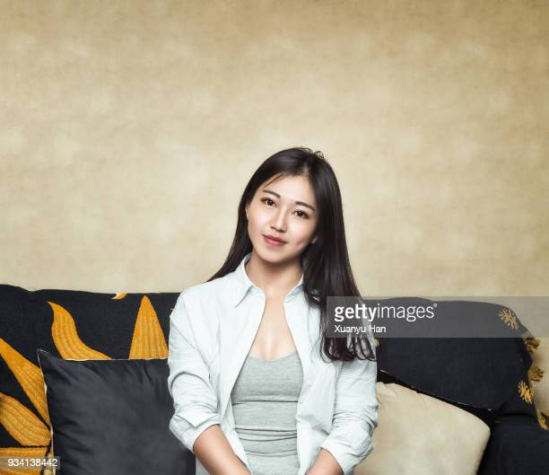 portrait of happy young woman sitting on sofa - 僅一名年輕女人 個照片及圖片檔