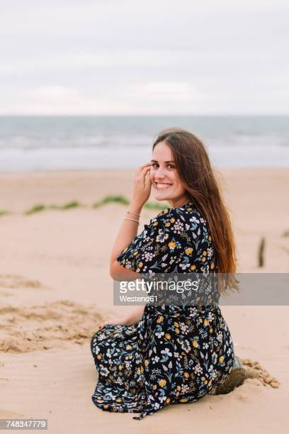 Portrait of happy young woman sitting on the beach