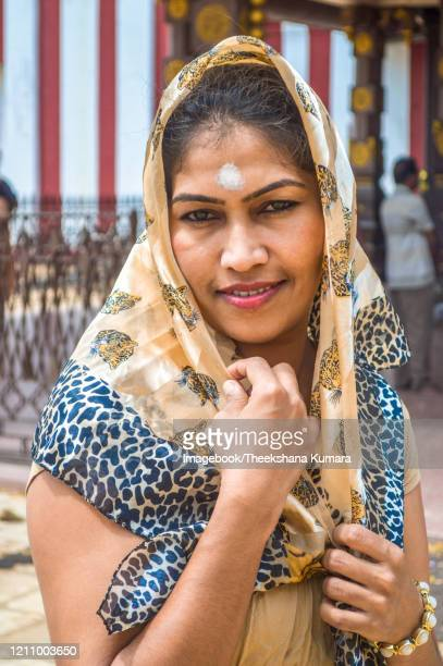 portrait of happy young woman standing front of the nallur kandaswamy kovil hindu temple (model - malee ranaweera) - imagebook stock pictures, royalty-free photos & images