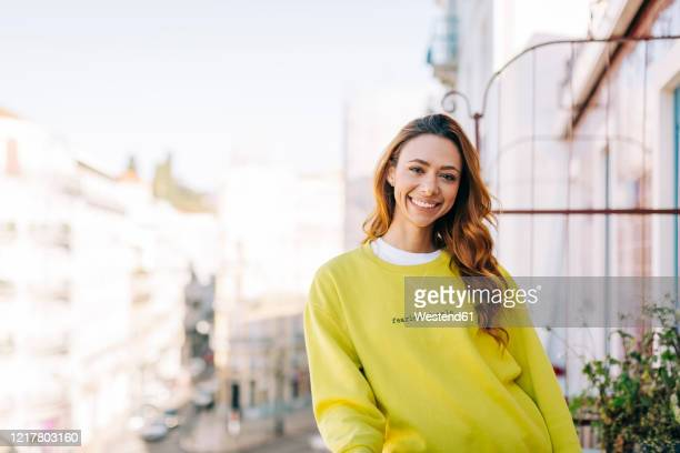 portrait of happy young woman standing on balcony - sweatshirt stock pictures, royalty-free photos & images