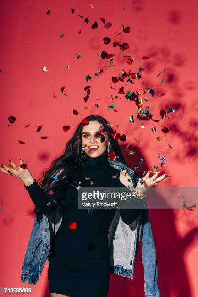 Portrait of happy young woman throwing confetti against coral background