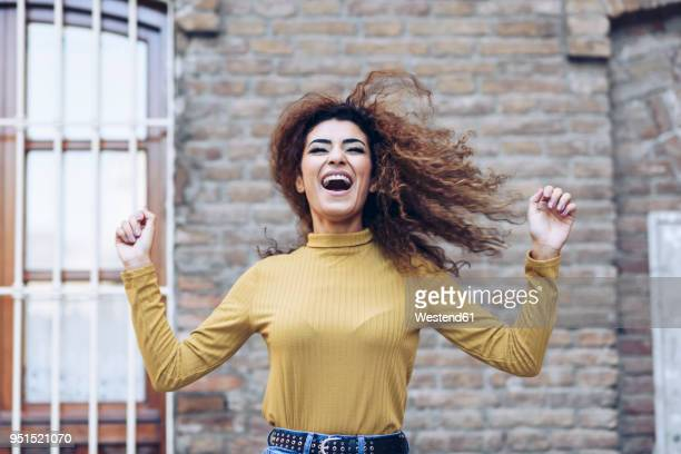 Portrait of happy young woman tossing her hair