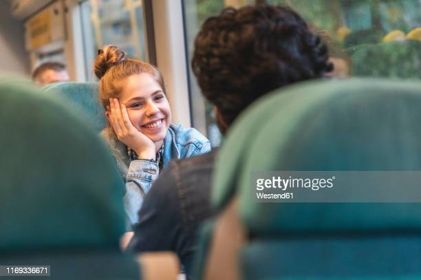 portrait of happy young woman travelling by train with her boyfriend, london, uk - flirting stock pictures, royalty-free photos & images