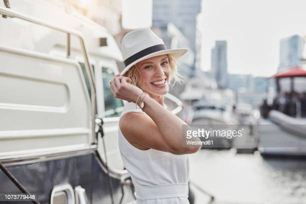 portrait of happy young woman wearing a hat at a marina next to a yacht - jetty stock pictures, royalty-free photos & images