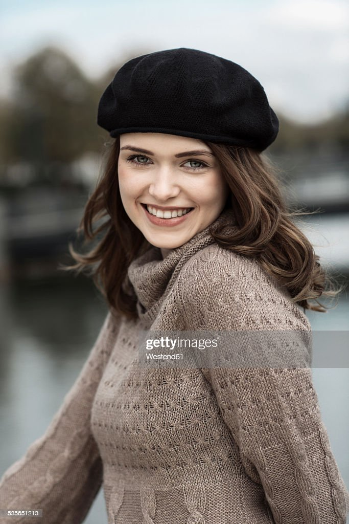 Portrait of happy young woman wearing beret and knitted dress   Stock Photo 3b4bfaa1a8b