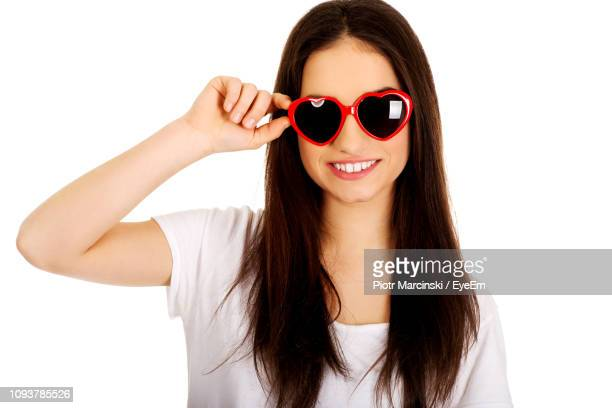 portrait of happy young woman wearing heart shaped sunglasses against white background - novelty item stock pictures, royalty-free photos & images