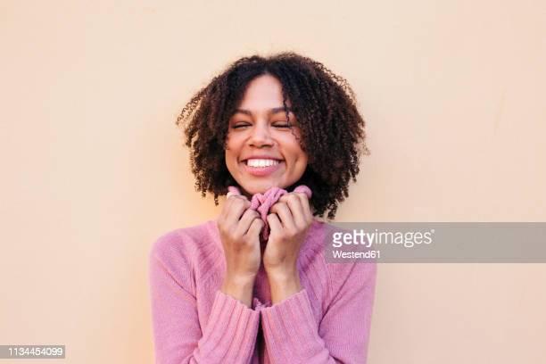 portrait of happy young woman wearing pink pullover - col roulé photos et images de collection