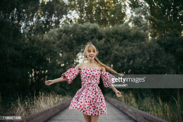 portrait of happy young woman wearing summer dress with floral design dancing on boardwalk - robe à motif floral photos et images de collection