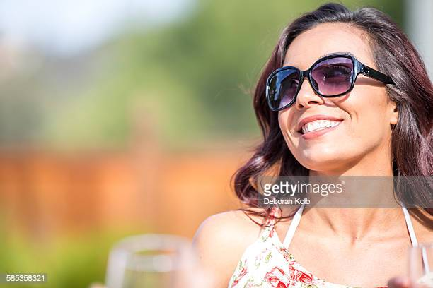 Portrait of happy young woman wearing sunglasses in garden