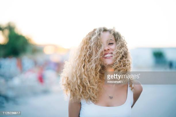 portrait of happy young woman with blond ringlets - cabelo encaracolado imagens e fotografias de stock