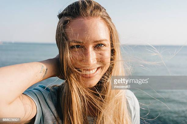 Portrait of happy young woman with blowing hair in front of the sea