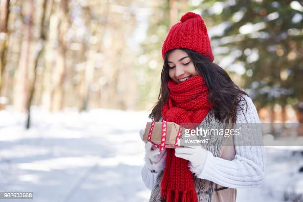 portrait of happy young woman with christmas gift in winter forest - country christmas stock pictures, royalty-free photos & images
