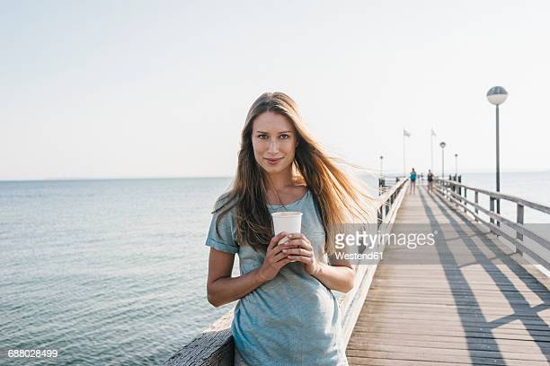Portrait of happy young woman with coffee to go on jetty