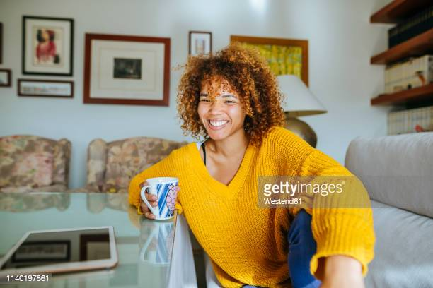 portrait of happy young woman with curly hair holding mug at home - looking at camera stock pictures, royalty-free photos & images