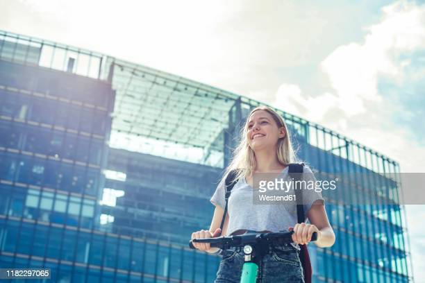 portrait of happy young woman with e-scooter in the city, berlin, germany - white shorts stock pictures, royalty-free photos & images