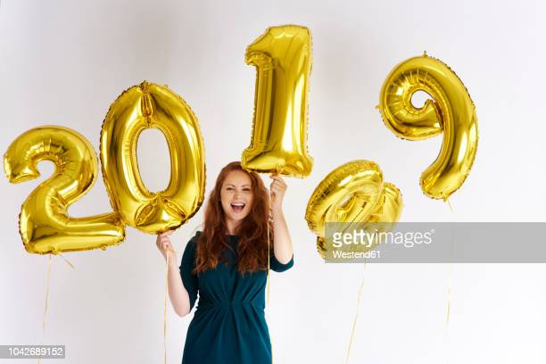 portrait of happy young woman with golden balloons forming the date '2019' - 2019 foto e immagini stock