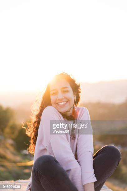 Portrait of happy young woman with long hair sitting on a wall at sunset