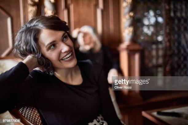 portrait of happy young woman with older woman in background - só adultos imagens e fotografias de stock