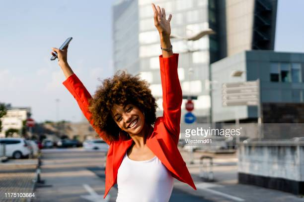 portrait of happy young woman with smartphone wearing fashionable red suit jacket - afro foto e immagini stock