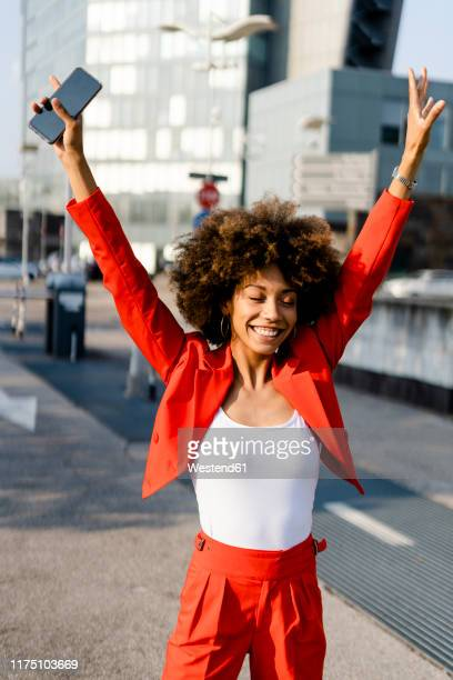 portrait of happy young woman with smartphone wearing fashionable red pantsuit - vertical stock pictures, royalty-free photos & images