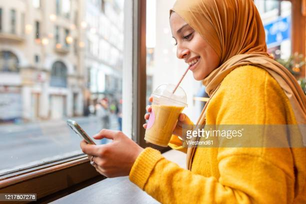 portrait of happy young woman with smoothie and smartphone in a cafe - islam stock pictures, royalty-free photos & images