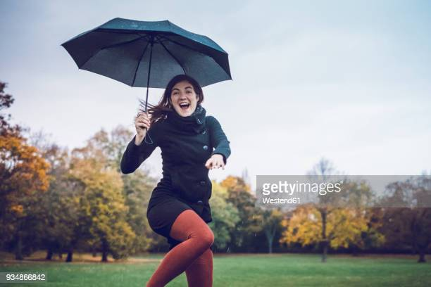 Portrait of happy young woman with umbrella dancing in autumnal park