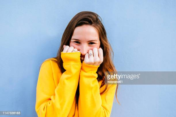 portrait of happy young woman with yellow pullover at blue wall - hands covering mouth stock pictures, royalty-free photos & images