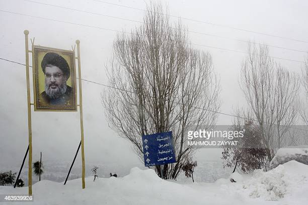 A portrait of Hassan Nasrallah the leader of Lebanese Hezbollah movement stands during a snowstorm in the Rihan Mountains region in southern Lebanon...