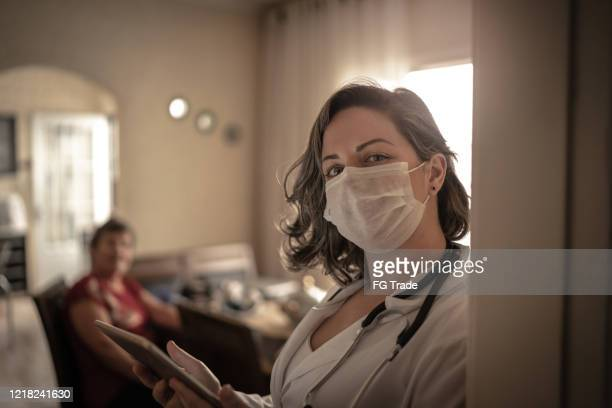 portrait of health visitor and a senior woman during home visit - visit stock pictures, royalty-free photos & images
