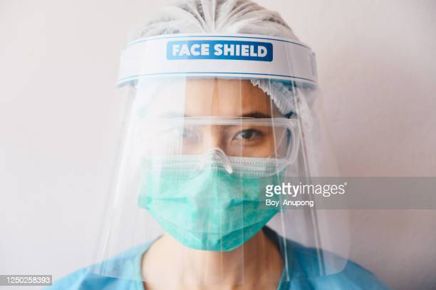 portrait of healthcare worker while wearing medical scrubs, mask and face shieldl before working in hospital during covid-19 pandemic. - フェイスシールド ストックフォトと画像