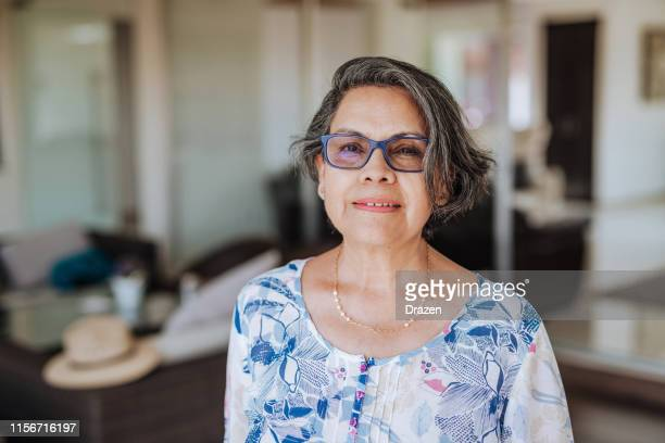 Portrait of healthy senior Latina woman with grey hair and glasses.