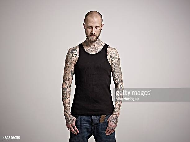 Portrait of heavily tattooed man in black vest.