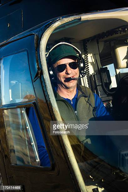portrait of helicopter pilot sitting in cockpit looking at viewer. - inside helicopter stock pictures, royalty-free photos & images