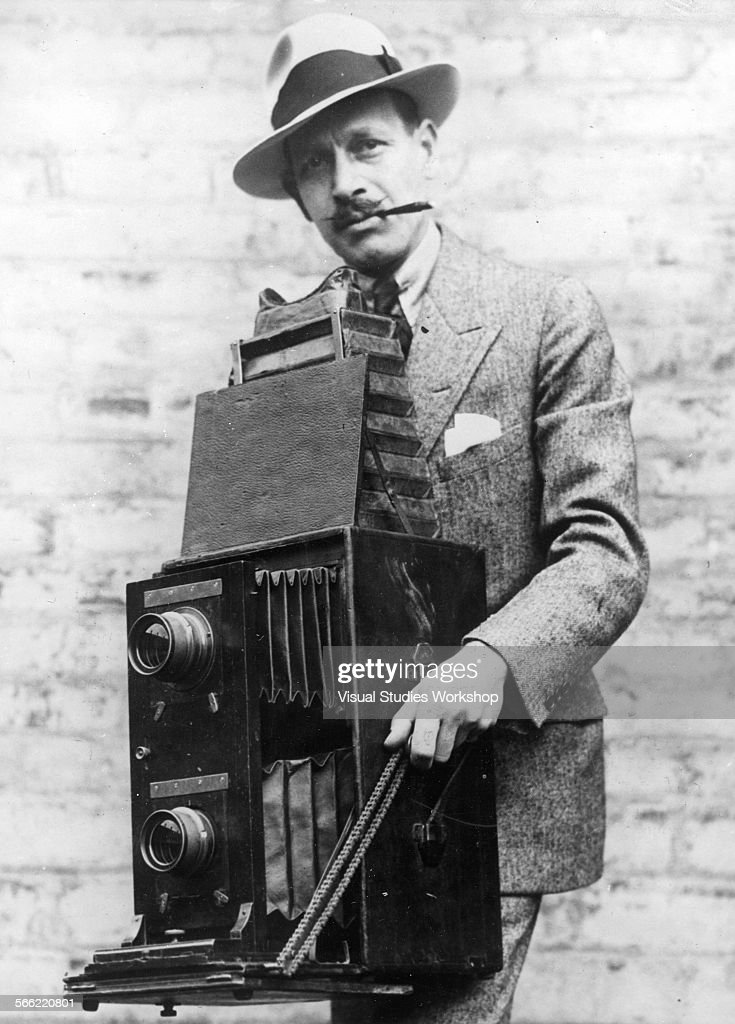 Portrait of Herman Haas, animal photographer, with his camera that weighs over 25 pounds, early to mid 20th century.