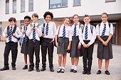 Portrait Of High School Student Group Wearing Uniform Standing Outside School Buildings