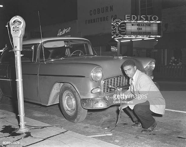 Portrait of high school student Shellie Lewis as he crouches down beside the grill of a Chevrolet Bel Air Orangeburg South Carolina 1958 He holds a...